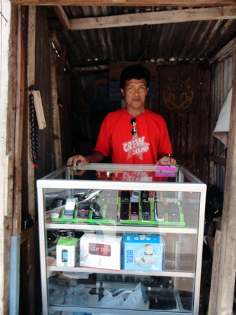 Rosyid awaiting customers in his shop where he sells secondhand mobile phones, handpon bekas, at prices the poor in Malang can afford.