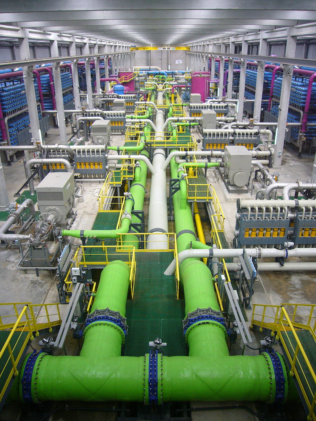 An image of a water processing plant showing color coded pipes and various containers they are leading to and from.