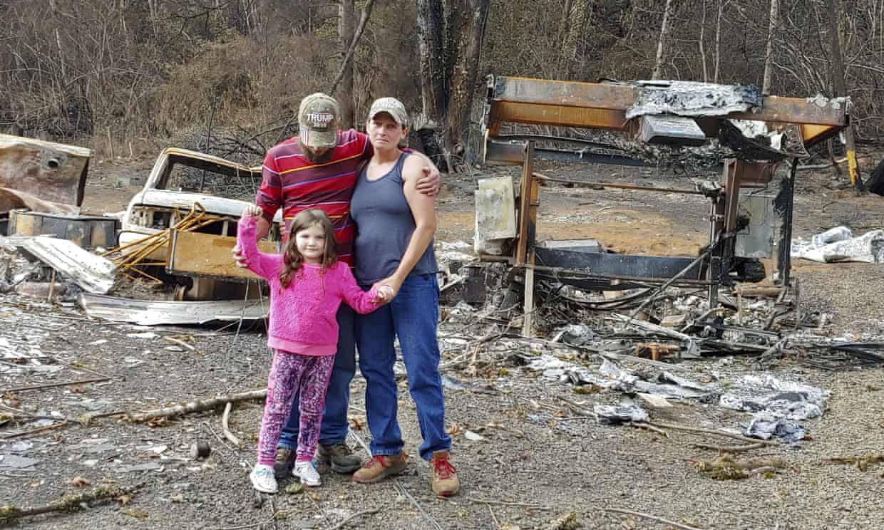 Family of three standing on the scorched land that was their home after it was destroyed by a wildfire