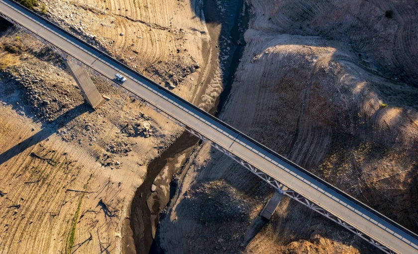 An aerial photo of a truck crossing a bridge over Lake Oroville which is only 1/3 full.