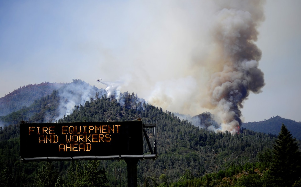 Plumes of smoke rising from forests with a sign saying fire equipment and workers ahead