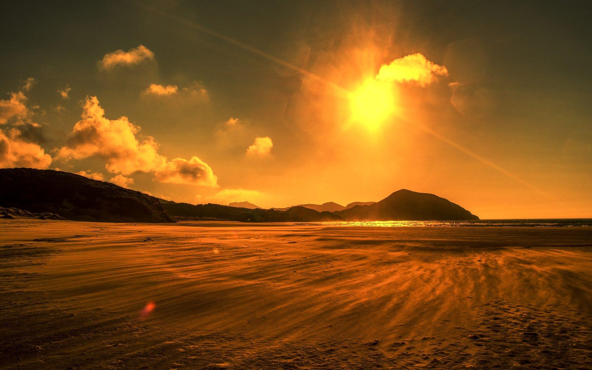 Beach with blazing sun in sky